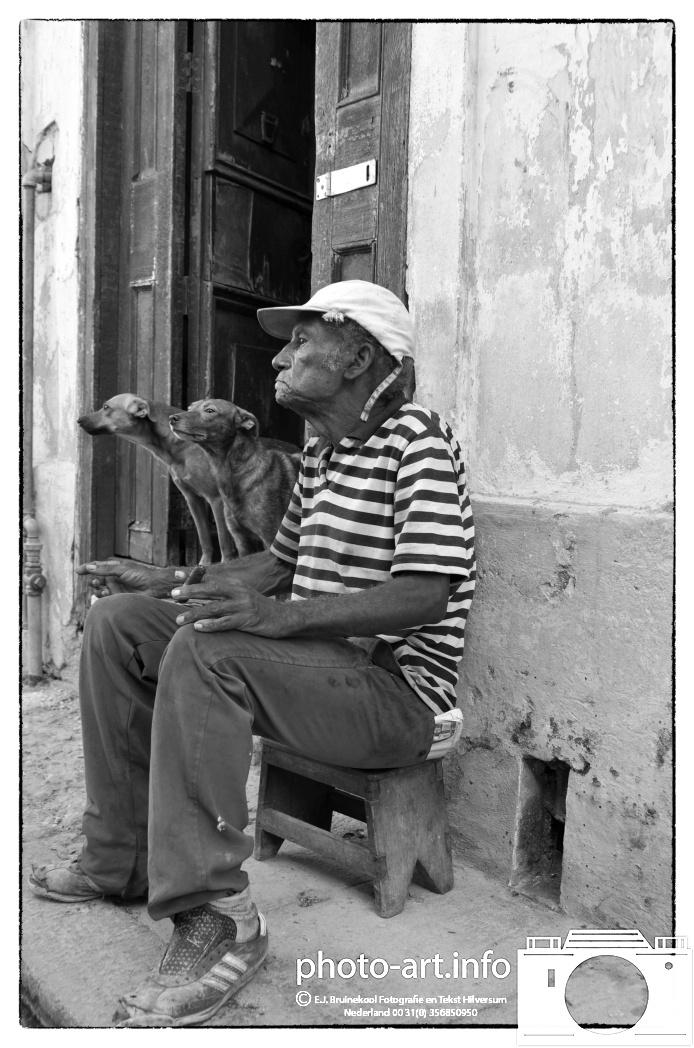 Cuba, Havana about 2.5 million inhabitants the largest city in Cuba. Elderly dogs for home on the sidewalk-Cuba, Havana ca. 2,5 miljoen inwoners de grootste stad van Cuba. Bejaard met honden voor het huis op de stoep-E.J.Bruinekool Fotografie Hilversum  Copyright naamsvermelding verplicht lid NVJ. Berlagelaan 62, 1222JZ,  Hilversum, Nederland, tel. 31(0)356850950, fax. 31 356479199