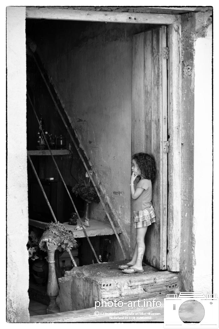 Trinidad State (since 1998) on the UNESCO World Heritage List. guying girl child at the front door--Trinidad staat (sinds 1998) op de Werelderfgoedlijst van UNESCO. kind meisje tuis bij de voordeur-E.J.Bruinekool Fotografie Hilversum  Copyright naamsvermelding verplicht lid NVJ. Berlagelaan 62, 1222JZ,  Hilversum, Nederland, tel. 31(0)356850950, fax. 31 356479199